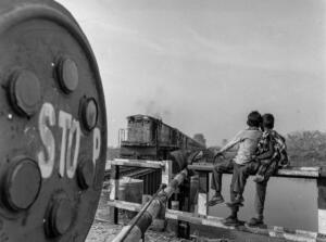 Kids love trains, whether they are inside or outside of them  Here two kids watch the passenger service to Bahraich pass the crossing at Manjhra Purab before heading off to the fields for cutting sugarcane